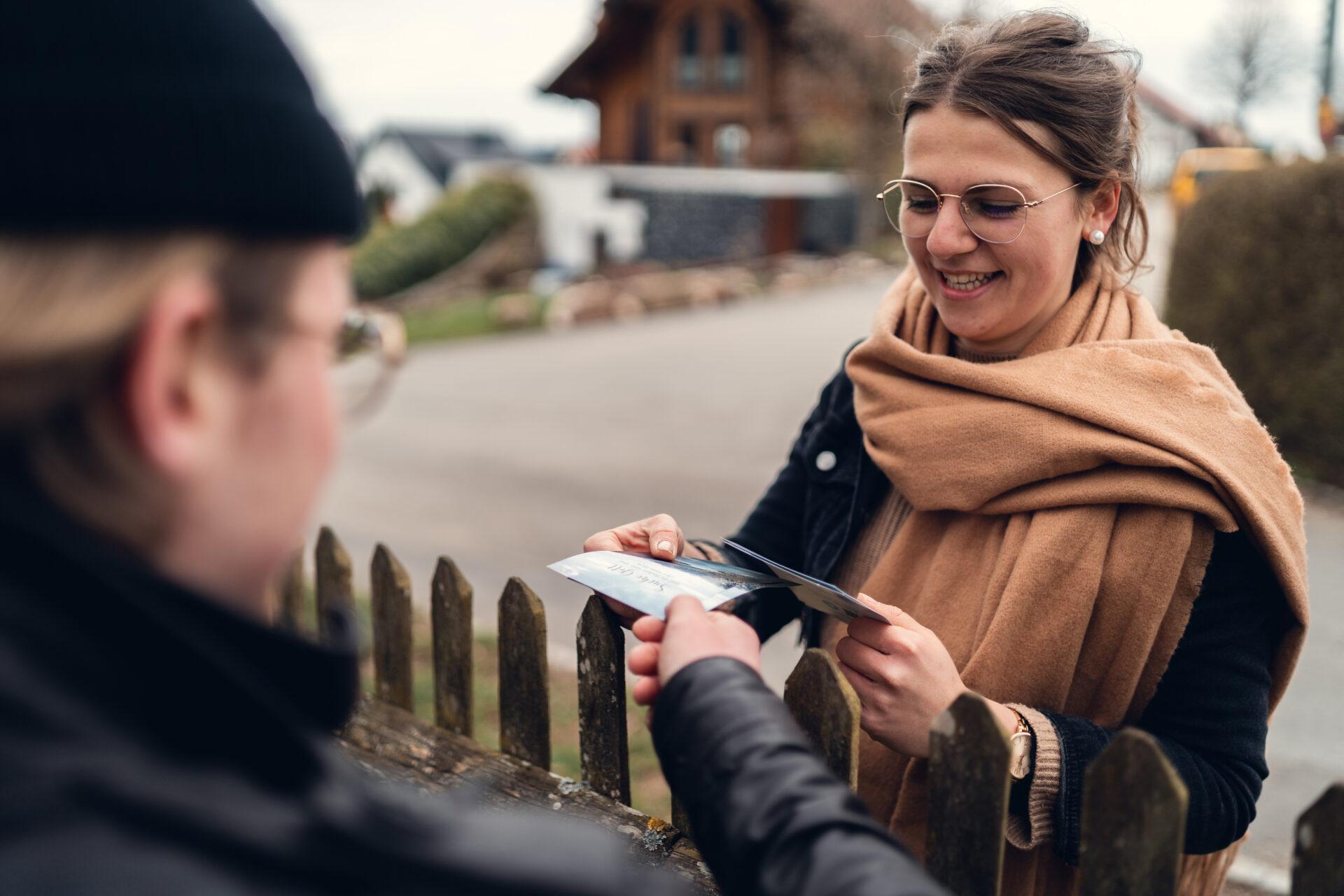 Junge Frau übergibt einen Flyer